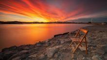 Stuhl vor weiter Landschaft mit feurigem Himmel